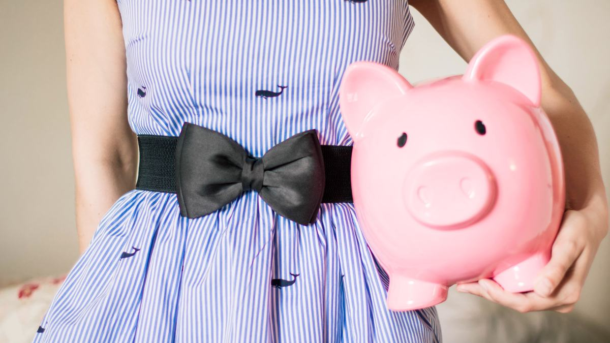 Woman in stripe dress holding pink piggy bank