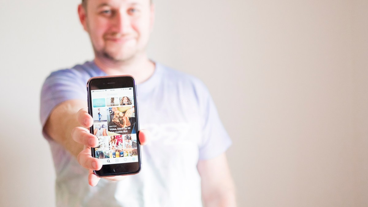 Man holding up phone with Instagram open