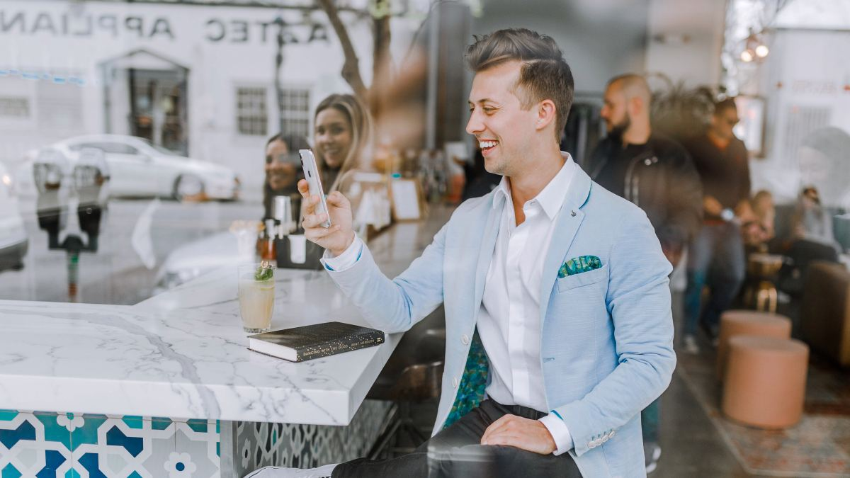Man sitting in coffee chop smiling at phone