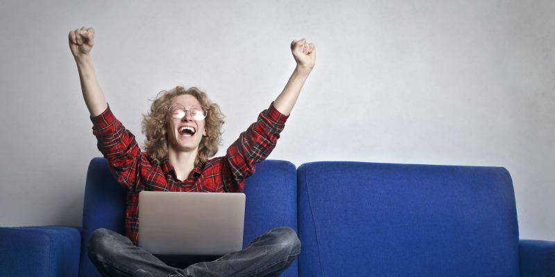 Person sitting on couch celebrating with hands in the air