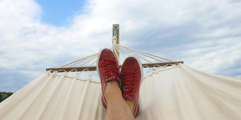 Shoes resting on hammock against the sky